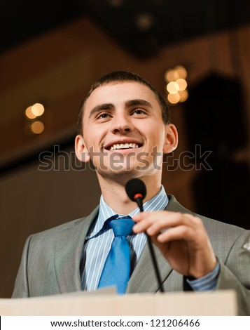 male speaker looks into the room and said into the microphone, speech at the conference - stock photo