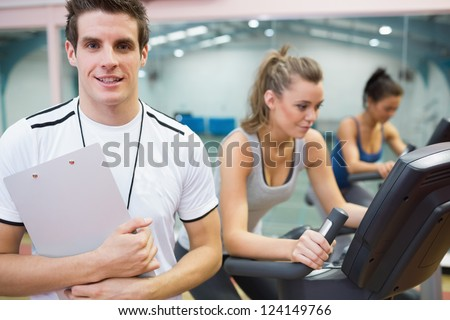 Male spinning class instructor holding clipboard with two women on exercise bikes - stock photo