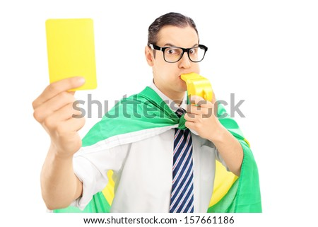Male sport fan with flag of Brazil holding a yellow card and blowing a whistle isolated on white background - stock photo
