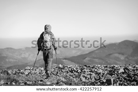 Male sportsman backpaker walking on the rocky top of the mountain with beautiful mountains on background. Man is wearing jacket and has trekking sticks and backpack on. black and white - stock photo