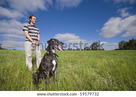 Male standing in meadow with dog on leash looking into horizon looking happy - stock photo