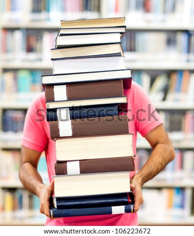 Male student carrying heavy books at the library - stock photo