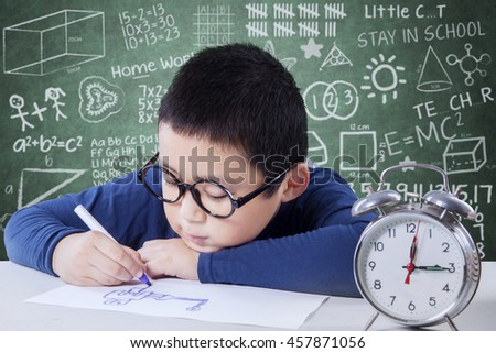 Male student drawing on the paper with a clock on the table, shot in the classroom