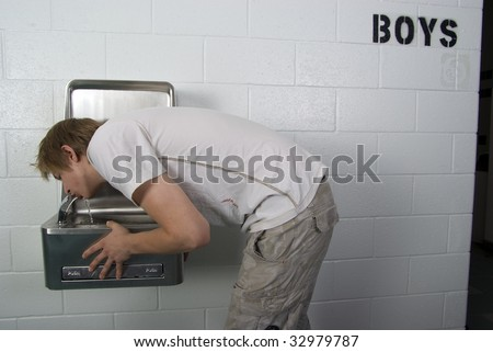 Male student drinks from school water fountain - stock photo