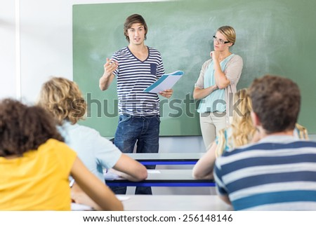 Male student explaining notes besides teacher in the class - stock photo