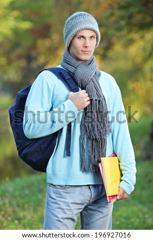 Male student holding books on a cold day outdoors - stock photo