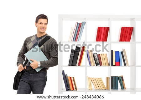 Male student leaning on a bookshelf isolated on white background - stock photo