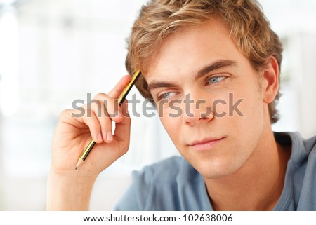 Male student preparing for exams at home thinking