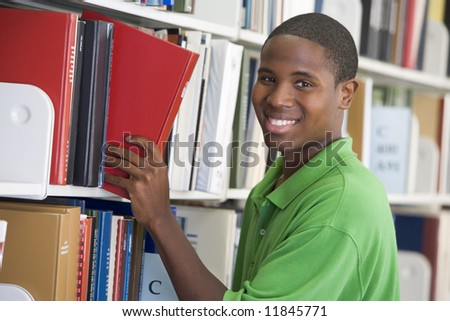 Male student selecting book in library - stock photo