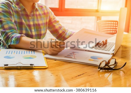 male student sitting at beautiful wooden desk and using digital computer while typing something on keyboard,freelancer working with laptop in home interior, morning light,selective focus,vintage color - stock photo