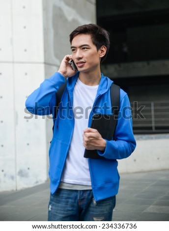 male student sitting with a mobile phone in her hand use laptop at campus - stock photo
