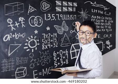 Male student smiling at the camera while holding a book and writing mathematics formula on the blackboard