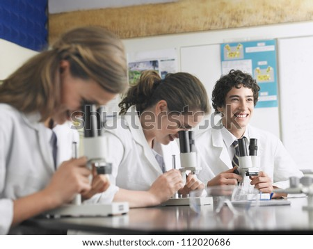 Male student smiling with microscope in hand and people in foreground - stock photo