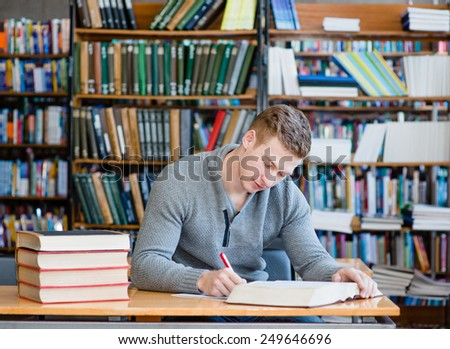 Male student studying in the university library - stock photo