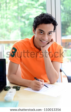 male student taking notes at the university - stock photo