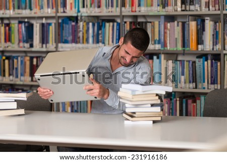 Male Student Throwing Laptop And Want To Destroy It - Shallow Depth Of Field - stock photo