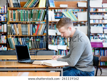 Male student with laptop studying in the university library - stock photo