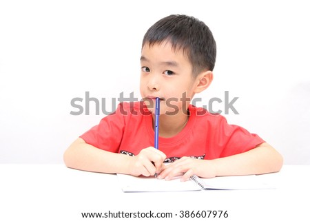 Male Student Working At Desk In Chinese School Classroom - stock photo