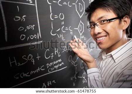 Male student working on difficult equation on blankboard