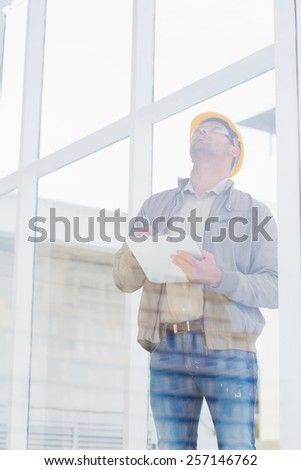Male supervisor looking up while writing on clipboard in office - stock photo