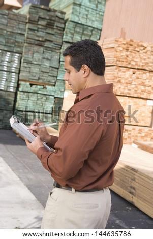 Male supervisor stock taking in warehouse - stock photo