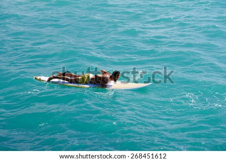 Male surfer floating on his surfboard in the waves of clean bight water, surfer man paddles out through the waves, handsome man enjoying a surf in clear blue water, sexy man surfing at the beach - stock photo