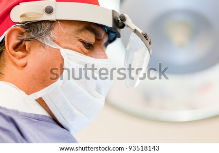 Male surgeon in the operating room with magnigying glasses - stock photo