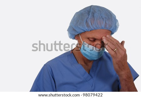 Male surgeon wearing scrubs and mask. Weary expression. Isolated on white. - stock photo