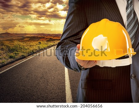 Male surveyor engineer standing on asphalt road through industrial fields holding protective hardhat for workers. Concept of successful start of construction project. - stock photo