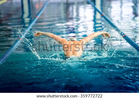Male swimmer performing the butterfly stroke at indoor swimming competition - stock photo
