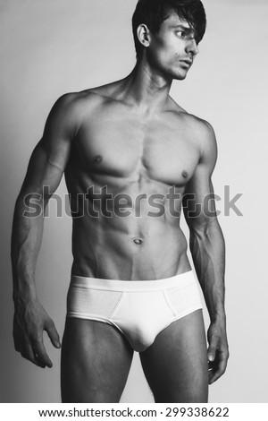 Male swimwear & underwear concept. Handsome muscular male model in trendy white underwear posing over grey background. Black & white photo. Studio shot - stock photo