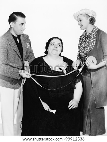 Male tailor and his assistant measuring an overweight woman with a measuring tape - stock photo