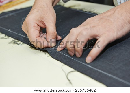 male tailor hands working with cloth fabric and needle in workshop - stock photo
