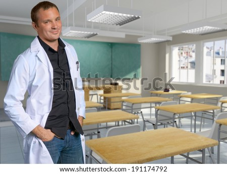 Male teacher in a white robe in a classroom - stock photo