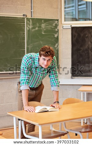 Male teacher standing at  the classroom, read book - stock photo