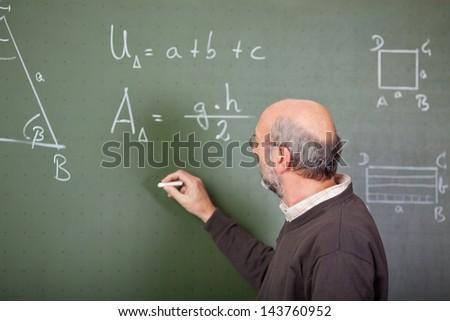 Male teacher writes on blackboard with a chalk - stock photo
