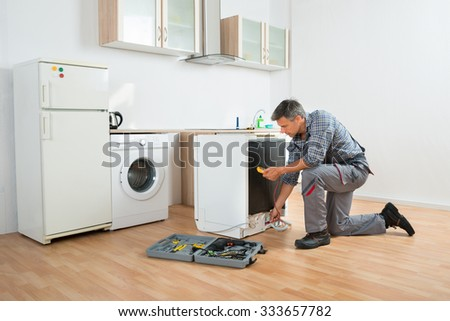 Male technician checking dishwasher with digital multimeter in kitchen - stock photo