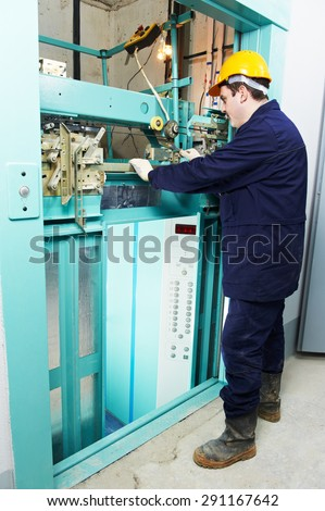male technician machinist worker adjusting elevator mechanism of lift with spanner - stock photo