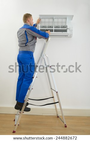 Male Technician Repairing Air Conditioner Standing On Stepladder - stock photo