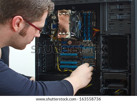 Male technician repairing computer at store - stock photo