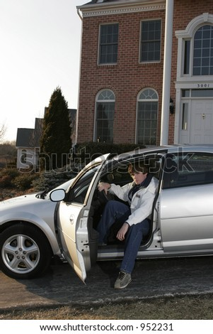 male teen getting out of car in upscale neighborhood - stock photo
