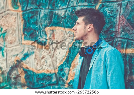 male teen standing on a graffiti wall with headphones - stock photo