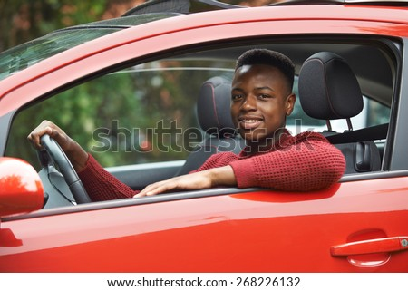 Male Teenage Driver Looking Out Of Car Window - stock photo