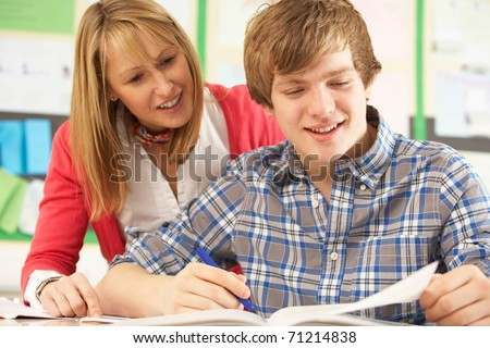 Male Teenage Student Studying In Classroom With Teacher