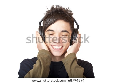 Male Teenager listening to music via headphone. Isolated on white background. - stock photo