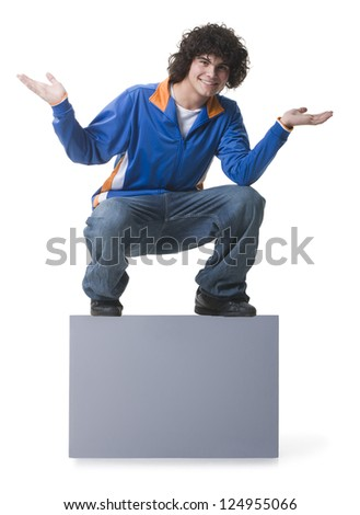 Male teenager sitting on blank sign