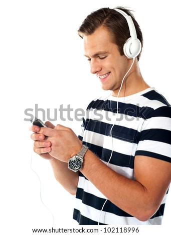 Male teenager with music player and ear buds listen to music. Surfing playlist