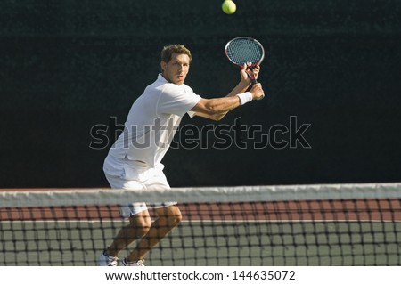 Male tennis player hitting backhand by net on the tennis court - stock photo
