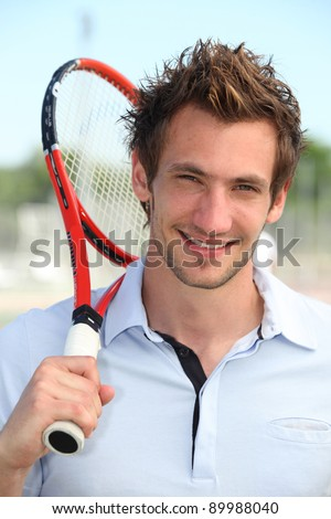 Male tennis player holding racquet over shoulder - stock photo