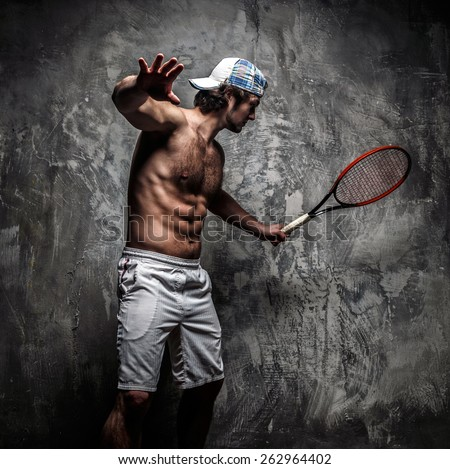 Male tennis player with racket in action.